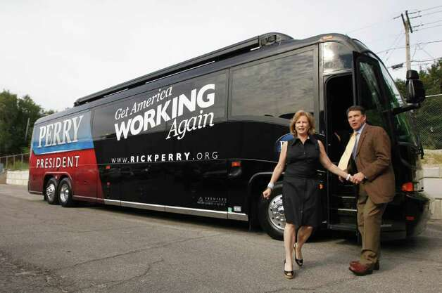 Republican presidential candidate, Texas Gov. Rick Perry and his wife Anita step off the campaign bus as they visit D.C. Taylor Roofing in Cedar Rapids, Iowa, Aug. 16, 2011. Photo: AP