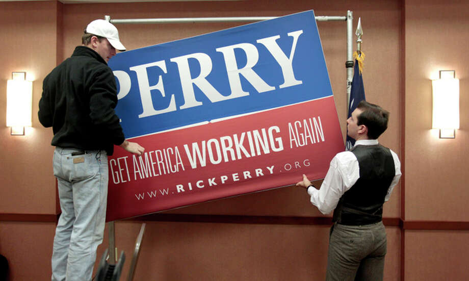 Campaign workers take down Perry's sign following the 11 a.m. news conference. Photo: David Goldman, Associated Press / AP