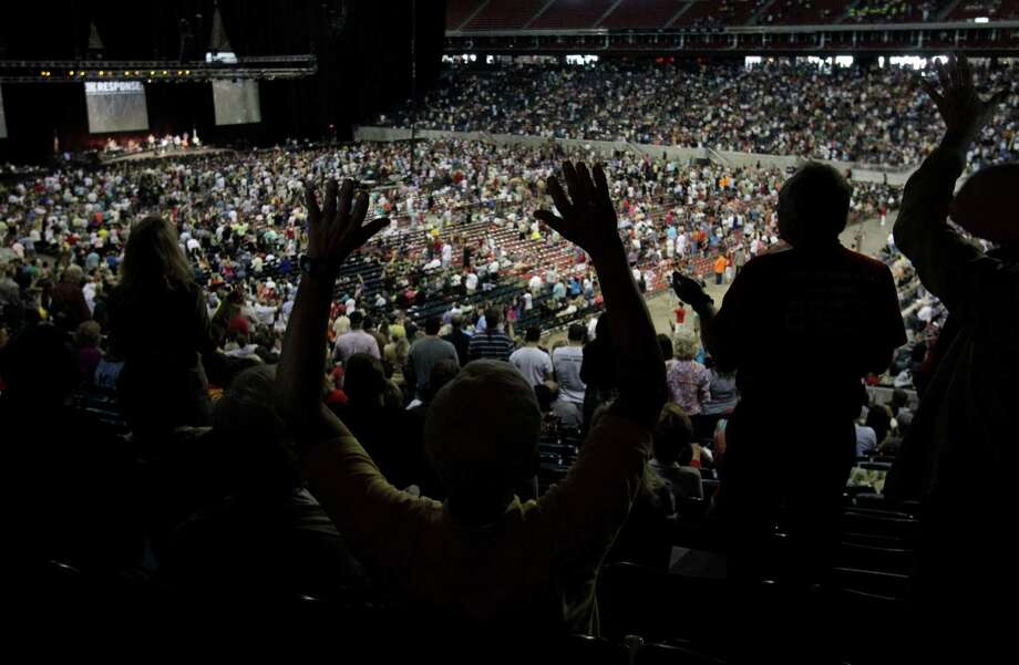 The governor drew 30,000 people to pray at Reliant Stadium in Houston, amid concern that the event mixed Perry's presidential ambitions and role as governor with his religious faith. Photo: Melissa Phillip, Houston Chronicle / © 2011 Houston Chronicle