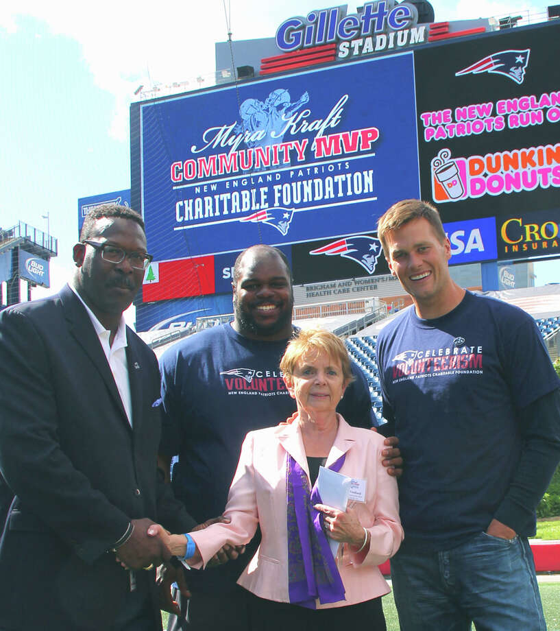 Shirley Fredlund of Voice for Joanie in New Milford is congratulated by, from right to left, New England Patriots quarterback Tom Brady and defensive lineman Vince Wilfork, and Hall of Famer Andre Tippett as one of 10 Myra Kraft Community MVP Award winners. Fredlund was presented with a $10,000 check for the organization. During the recent luncheon in Foxboro, Mass., the Kraft family awarded $200,000 in grants to 26 New England nonprofits.  Courtesy of the Kraft family Photo: Contributed Photo / The News-Times Contributed