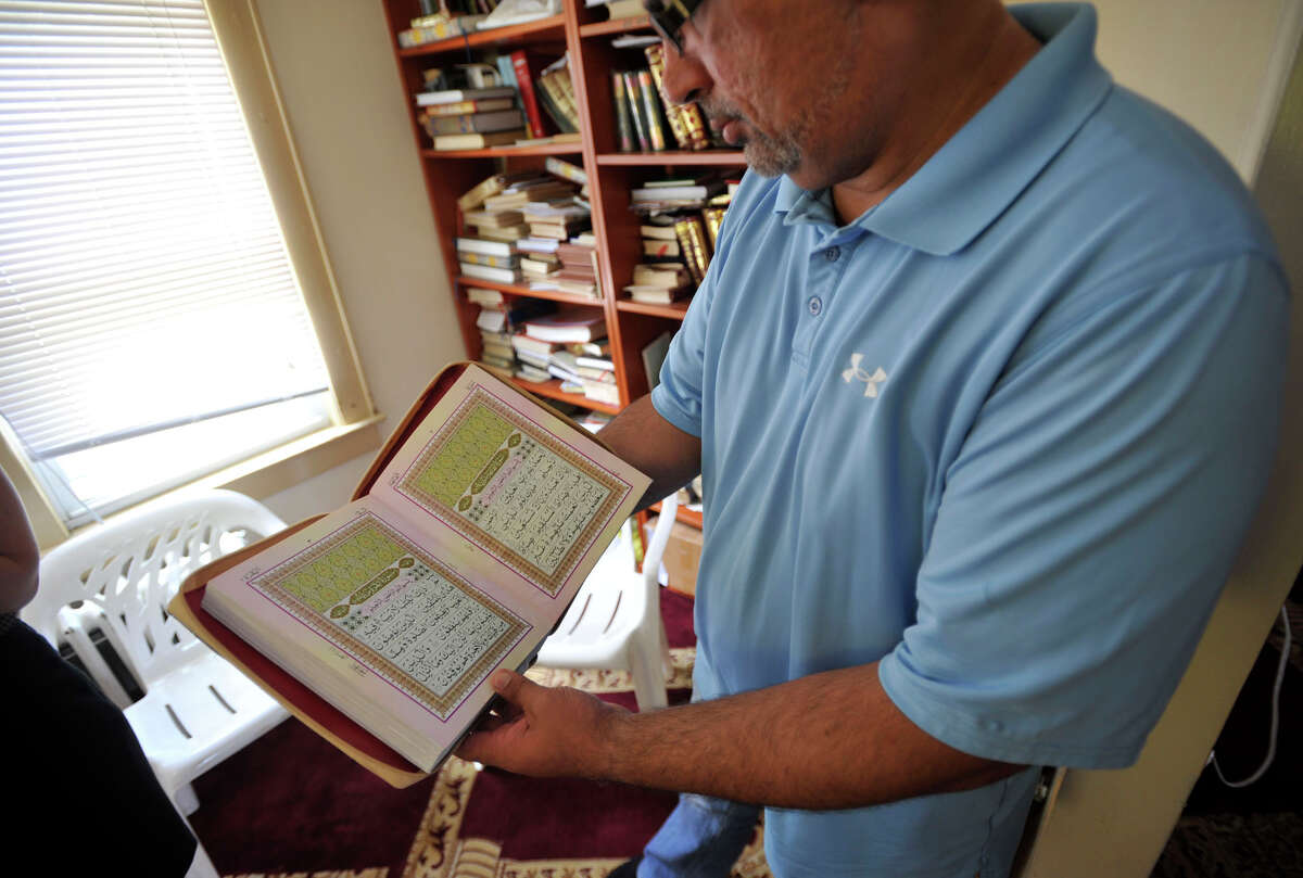 Shahzad Khawaja displays a Qur'an at the current home to the Stamford Islamic Center on Outlook Street in Stamford on Monday, July 8, 2013. The center is moving to a place that is currently under construction next door on West Avenue.