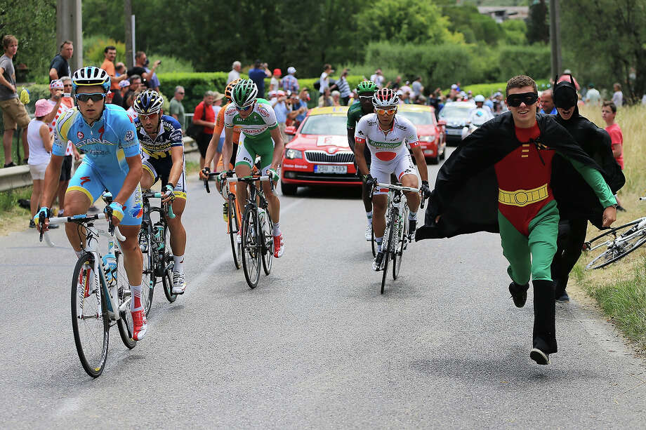 Fans dressed as Batman and Robin run alongside the riders including Yukiya Arashiro of Japan and Team Europcar (C)  during stage five of the 2013 Tour de France, a 228.5KM road stage from Cagnes-sur-mer to Marseille, on July 3, 2013 in Marseille, France. Photo: Doug Pensinger, Getty Images / 2013 Getty Images