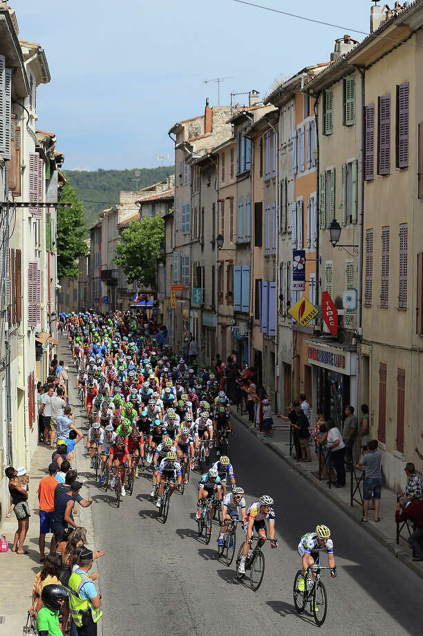 The peloton passes through town as they approach the final climb of the day during stage five of the 2013 Tour de France, a 228.5KM road stage from Cagnes-sur-mer to Marseille, on July 3, 2013 in Cuge-les-Pins, France. Photo: Doug Pensinger, Getty Images / 2013 Getty Images