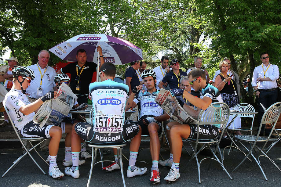 Gert Steegmans (2nd R) of Belgium and Team Omega Pharma-Quick Step and his team-mates read newspapers prior to stage eight of the 2013 Tour de France, a 195KM road stage from Castres to Ax 3 Domaines, on July 6, 2013 in Castres, France. Photo: Bryn Lennon, Getty Images / 2013 Getty Images