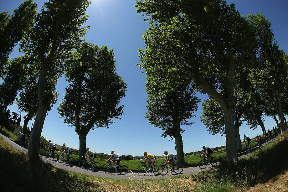 Team Orica Greenedge (L) and team Sky Procycling pass through the countryside during stage eight of the 2013 Tour de France, a 195KM road stage from Castres to Ax 3 Domaines, on July 6, 2013 in Ax 3 Domaines, France. Photo: Bryn Lennon, Getty Images / 2013 Getty Images