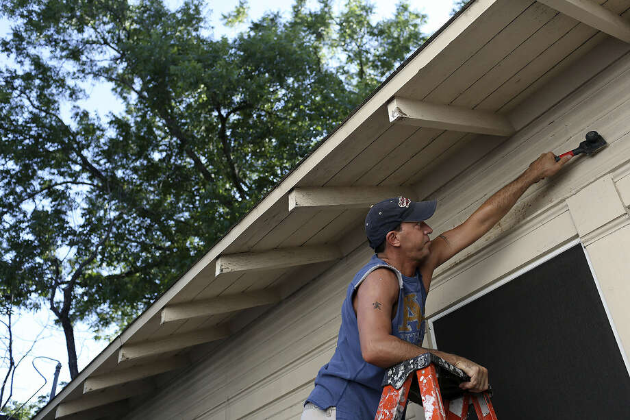 Volunteer David Laidacker, with CVS Caremark, strips a home to be painted in the Highland Park neighborhood in San Antonio June 29. Photo: Lisa Krantz / San Antonio Express-News