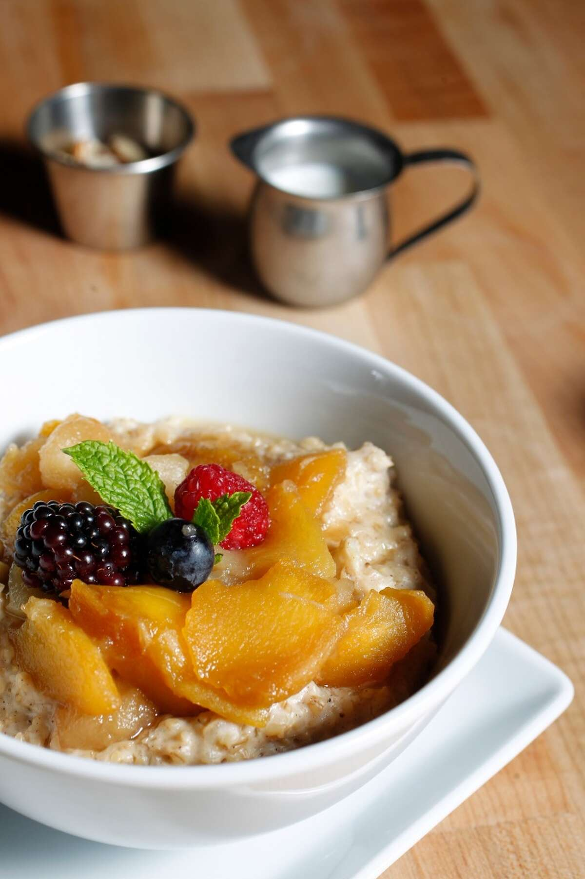 Steel Cut Oats with Seasonal Fruit Compote is served at Adair Kitchen with almonds and milk.