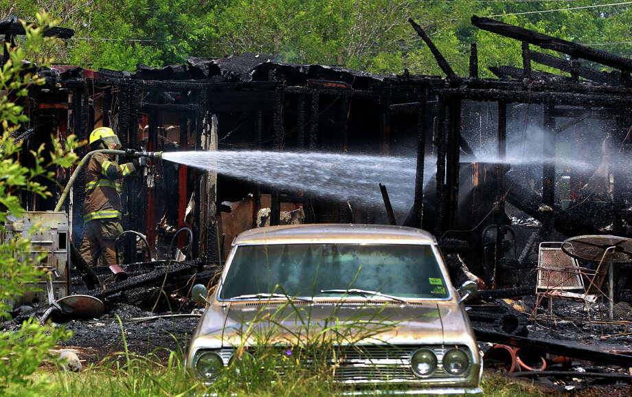 County firefighters spray water on the remains of a house that burned down Monday in southwest Bexar County. Photo: John Davenport, San Antonio Express-News / ©San Antonio Express-News/Photo may be sold to the public