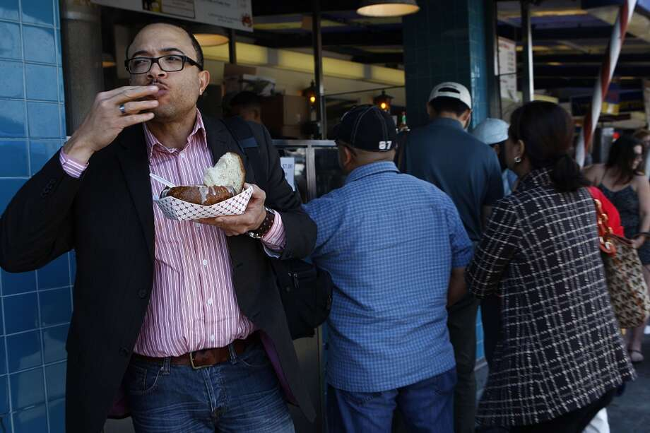 Bradley Pascal (left) from Atlanta has clam chowder in a sourdough bowl from Alioto's crab stand.