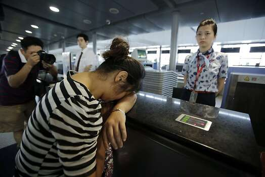 An unidentified family member of one of two Chinese students killed in a crash of an Asiana Airlines' plane on Saturday, cries at the airline's counter as she and other family members check in for a flight to San Francisco, at Pudong International Airport in Shanghai, China, Monday, July 8, 2013. The Asiana flight crashed upon landing Saturday, at San Francisco International Airport, and two of the 307 passengers aboard were killed. Photo: Eugene Hoshiko, Associated Press