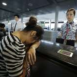 An unidentified family member of one of two Chinese students killed in a crash of an Asiana Airlines' plane on Saturday, cries at the airline's counter as she and other family members check in for a flight to San Francisco, at Pudong International Airport in Shanghai, China, Monday, July 8, 2013. The Asiana flight crashed upon landing Saturday, at San Francisco International Airport, and two of the 307 passengers aboard were killed.
