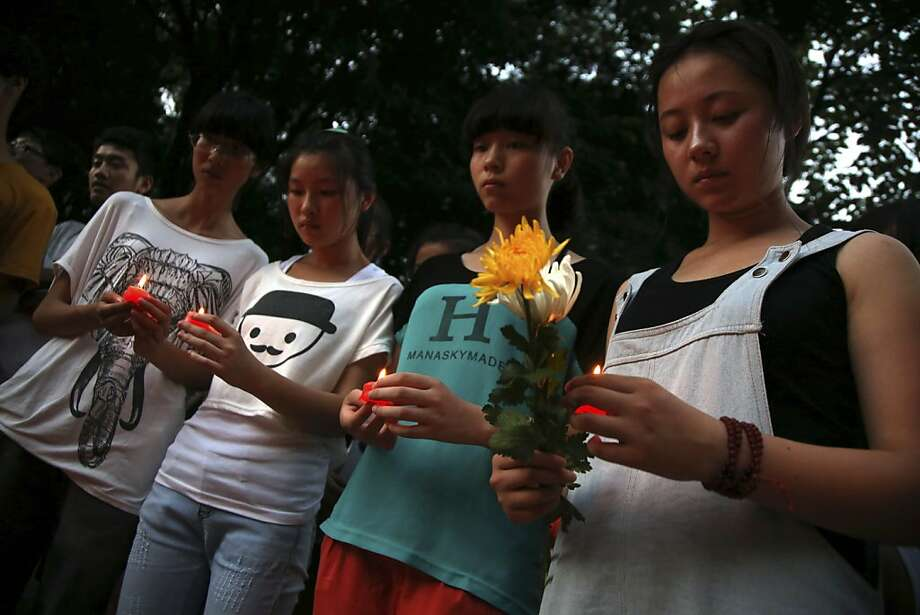 Residents gather to mourn for the two victims of the Asiana airline plane crash in San Francisco at a park in Jiangshan city in eastern China's Zhejiang province on Monday, July 8 2013. Chinese state media and Asiana Airlines have identified the two victims of the Asiana Airlines crash at San Francisco International Airport girls as Ye Mengyuan and Wang Linjia, students in Zhejiang, an affluent coastal province in eastern China. Photo: Associated Press