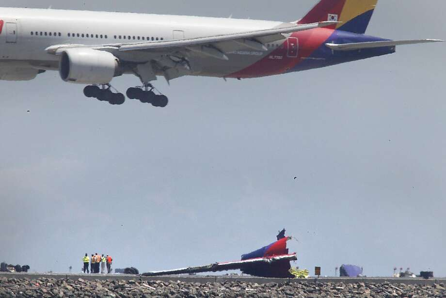 Officials from National Transportation Safety Board (NTSB) walk near the debris of the tail section of Asiana Flight 214 as they continued investigating the crash of Flight 214 as an Asiana airplane passes above during landing (top) on Monday, July 8, 2013 at San Francisco International Airport. Photo: Lea Suzuki, The Chronicle