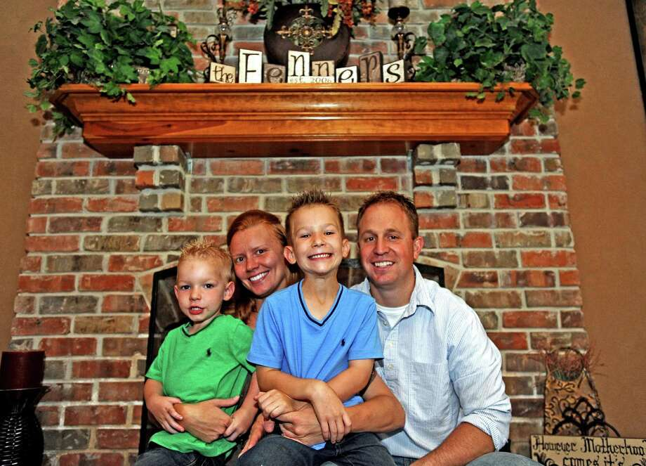 The Fenner family, from left to right; James, Rachel, Michael, and Jonathan sit tight at the fire place in their home on Saturday, July 6, 2013. Photo taken: Randy Edwards/The Enterprise