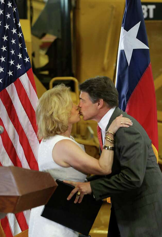 Texas Gov. Rick Perry kisses his wife Anita Perry as he prepares to announce he is not seeking re-election on Monday, July, 8, 2013, during an announcement at Holt Cat Co. in San Antonio. Photo: Bob Owen, San Antonio Express-News / ©2013 San Antonio Express-News
