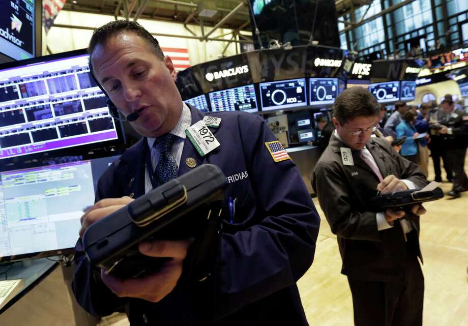 Trader Jonathan Corpina, left, works on the floor of the New York Stock Exchange Monday, July 8, 2013. Stocks rose in early trading Monday ahead of the start of second-quarter corporate earnings reports. (AP Photo/Richard Drew) ORG XMIT: NYRD102 Photo: Richard Drew / AP