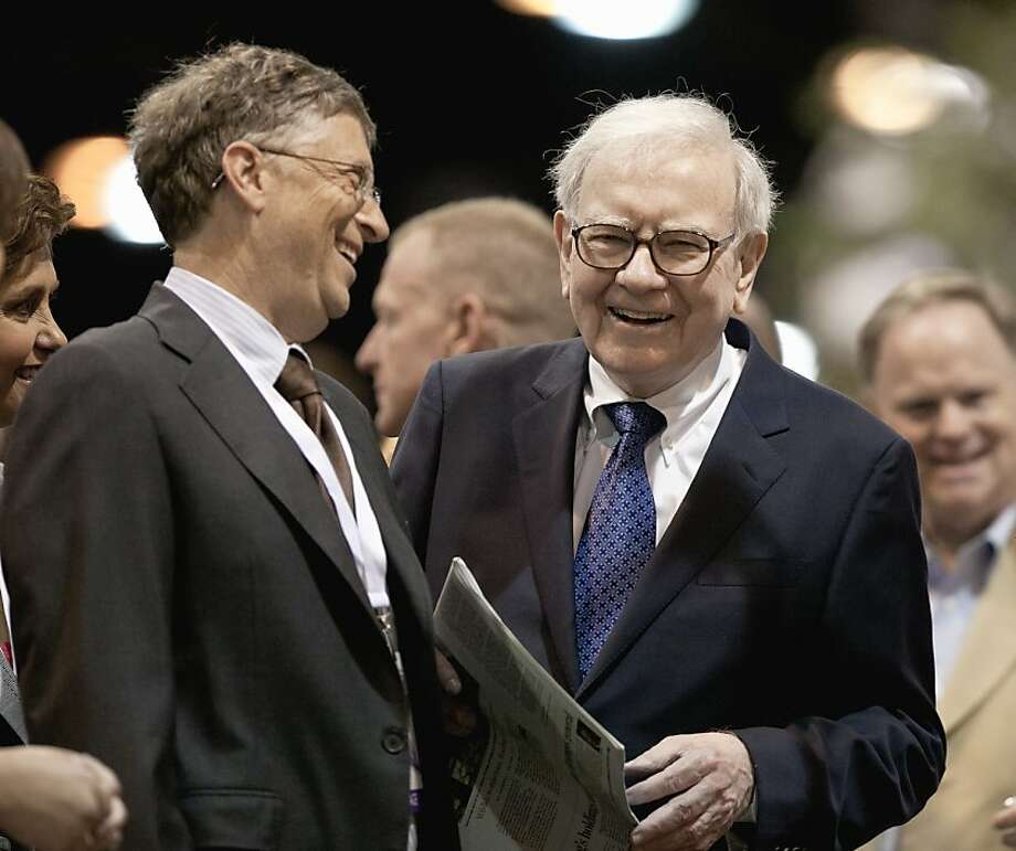 Warren Buffett, chairman and CEO of Berkshire Hathaway, right, and Bill Gates joke during a newspaper tossing competition in Omaha, Neb., Saturday, May 5, 2012. Berkshire Hathaway is holding it's annual shareholders meeting this weekend. (AP Photo/Nati Harnik) Photo: Nati Harnik, Associated Press