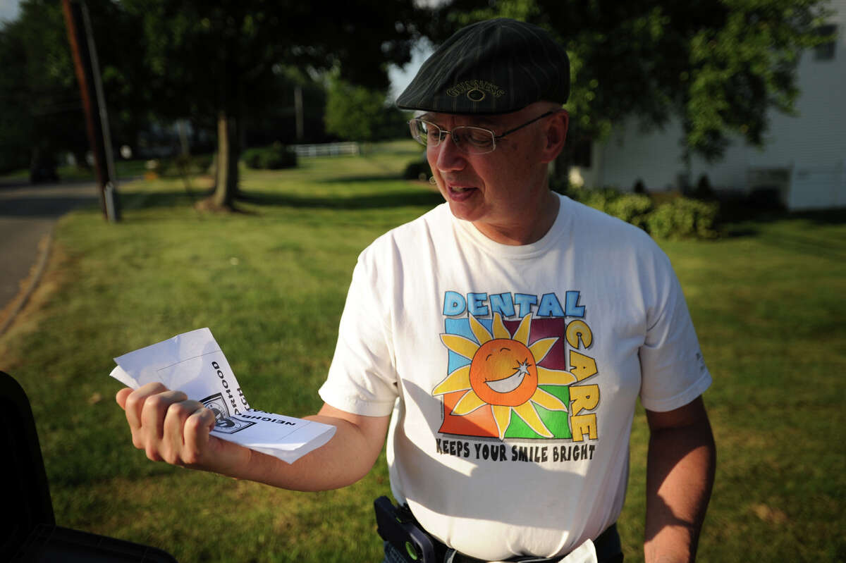 Dentist Dr. John Vecchitto picks up a Ku Klux Klan flier left on his Herbert Street driveway in Milford, Conn. on Monday, July 8, 2013.