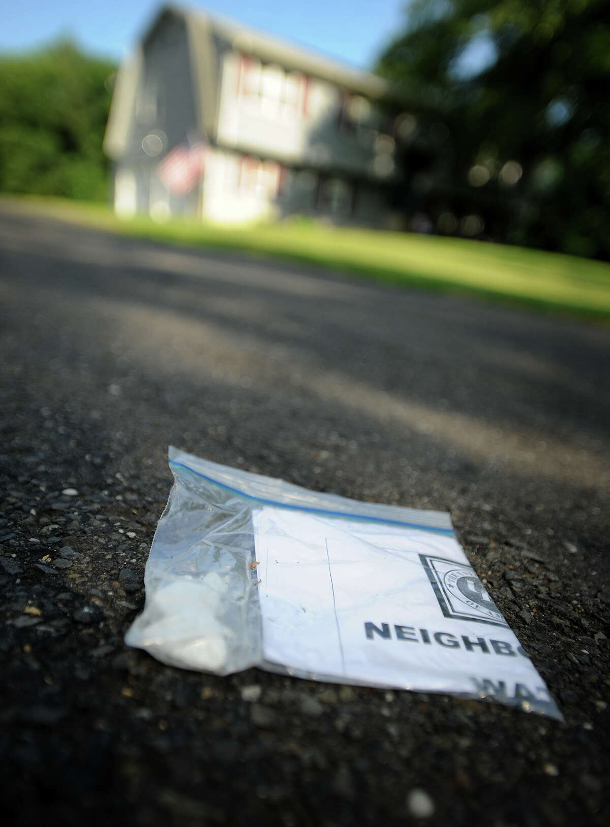 A Ku Klux Klan flier is folded in a plastic baggie held down with small white rocks at the end of a driveway on Coram Lane in Milford, Conn. on Monday, July 8, 2013.