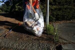 Mary Forte ties up a bag of litter for the city to collect in her neighborhood in East Oakland on June 29, 2013.  Forte goes out every week to clean up the area around the street where she has resided for 63 years. As part of the 'Keep Oakland Beautiful' effort, Forte volunteers to help keep Blandon and Glenly Road clean from garbage.
