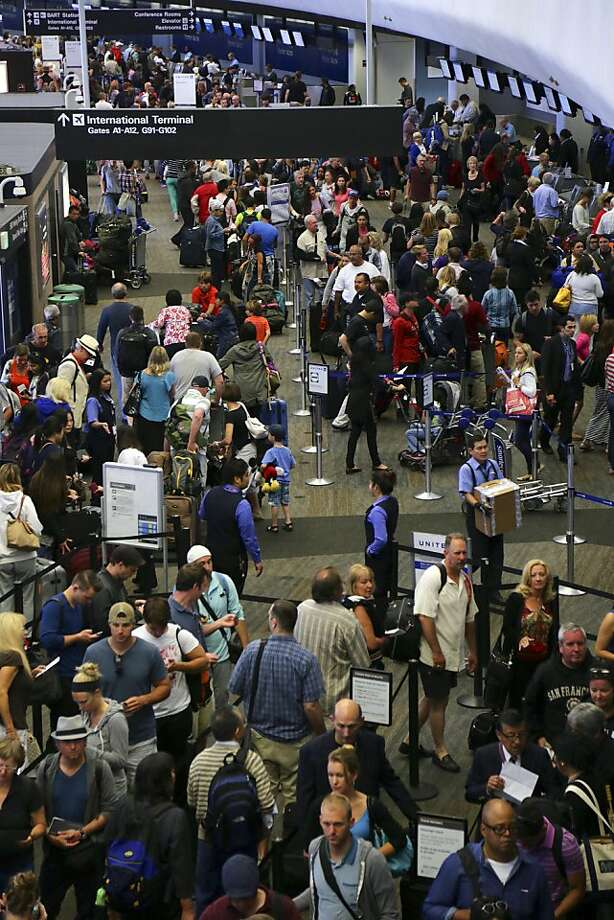 Passengers wait to speak to airline agents in a crowded terminal at San Francisco International Airport a day after the Asiana Airlines flight crash. Photo: Jim Wilson, New York Times