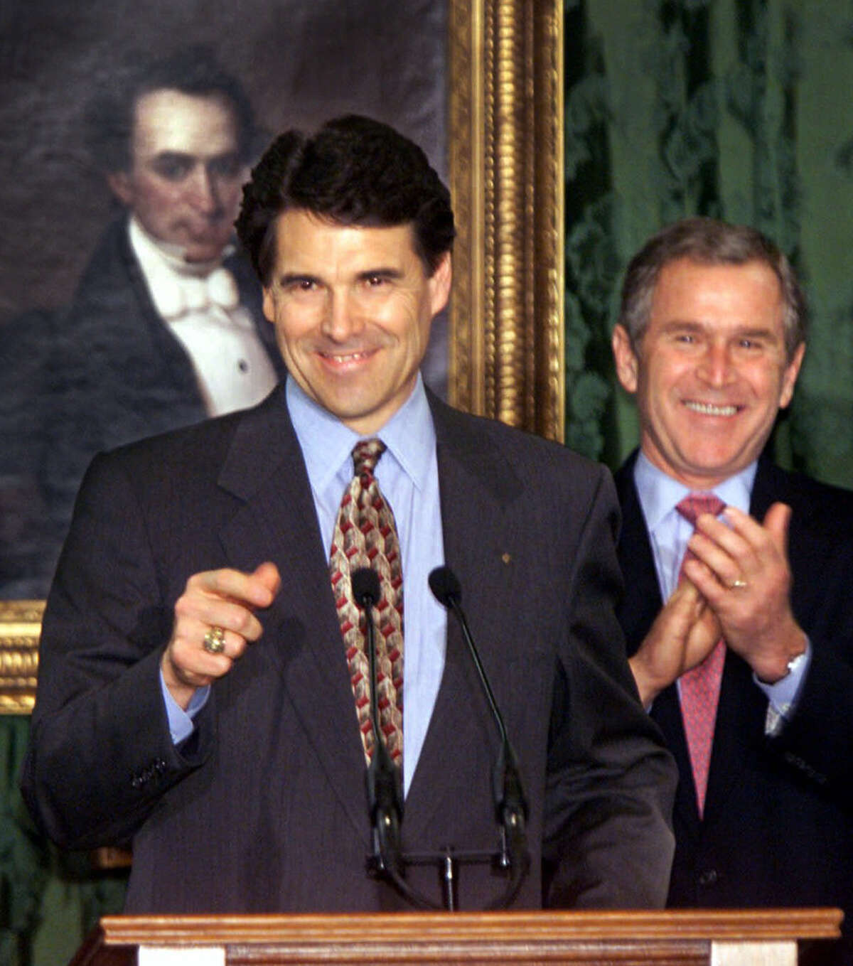 With President-elect George W. Bush beside him, Rick Perry is sworn in as Texas governor in 2000.