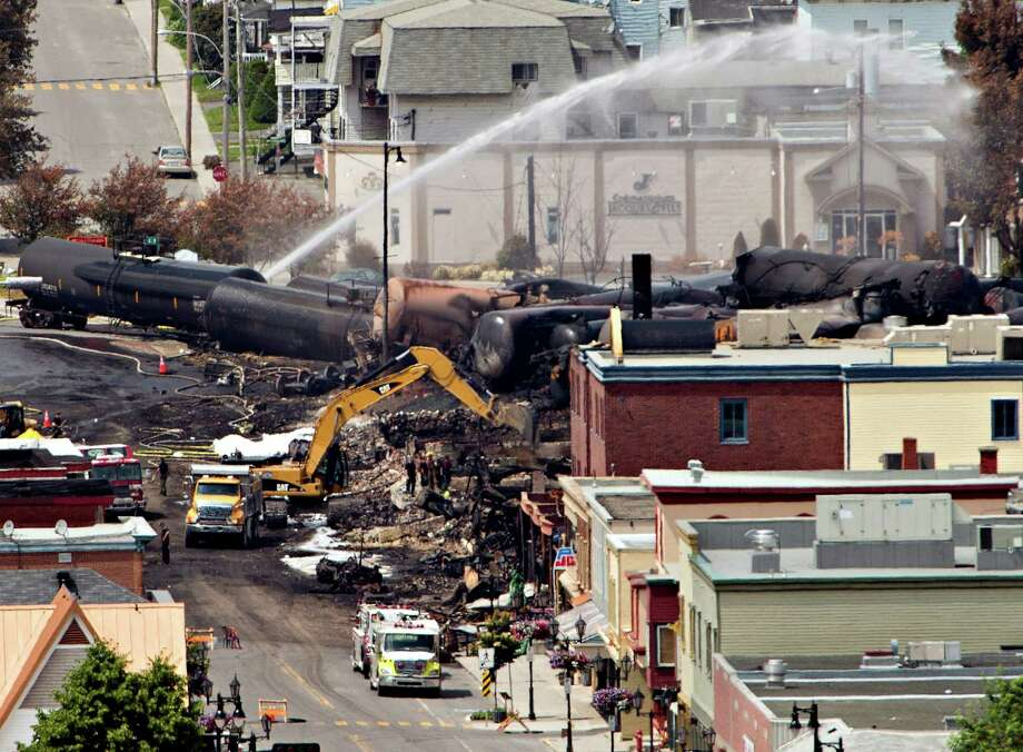 Searchers dig through the rubble for victims of the inferno in Lac-Megantic, Quebec, Monday, July 8, 2013, as  firefighter continue to hose down tanker cars to prevent explosions.  A runaway train derailed igniting tanker cars carrying crude oil early Saturday.  (AP Photo/ THE CANADIAN PRESS,Ryan Remiorz) Photo: Ryan Remiorz, STF / CP