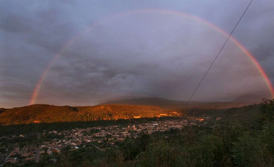 A rainbow forms over the town of Santiago Xalizintla where the Popocatepetl volcano, behind center, is covered by clouds in Mexico, Monday, July 8, 2013. The Environment Ministry has urged residents to take preventive measures to deal with the ash, including wearing dust masks, covering water supplies and staying indoors as needed. (AP Photo/Marco Ugarte) Photo: Marco Ugarte, Associated Press