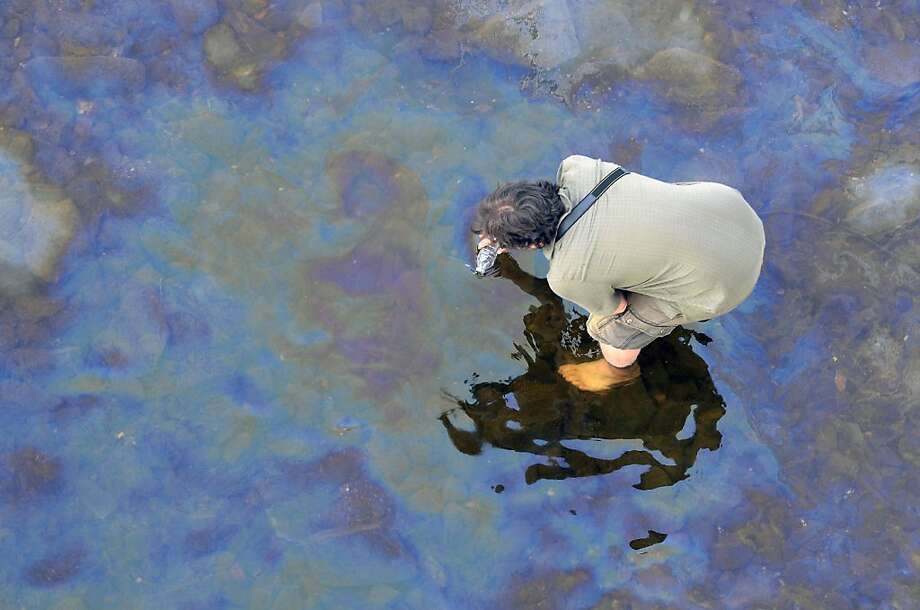 TOPSHOTS A worker inspects oil on the Chaudière River July 8, 2013 near Lac-Megantic, two days after a massive explosion caused by a runaway oil tanker train derailed and flattened part of the small Canadian town. The death toll has risen to 13, a coroner said July 8th, and dozens more remain missing.    AFP  PHOTO /  STEEVE DUGUAYSTEEVE DUGUAY/AFP/Getty Images Photo: Steeve Duguay, AFP/Getty Images