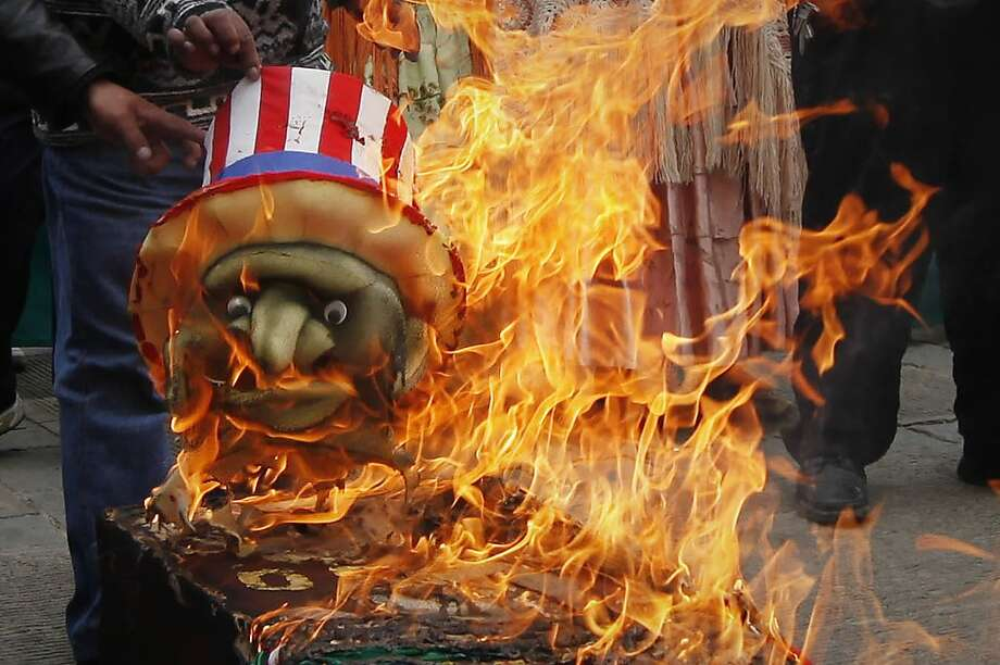 Demonstrators burn a coffin and a replica of Uncle Sam outside the U.S. embassy in La Paz, Bolivia, Monday, July 8, 2013. Bolivia's President Evo Morales has accused the United States of pressuring European governments to deny his plane permission to enter their airspace amid suspicions that NSA leaker Edward Snowden might have been onboard. Venezuela and Bolivia both made asylum offers to Snowden over the weekend, and Nicaragua has said it is also considering his request. (AP Photo/Juan Karita) Photo: Juan Karita, Associated Press