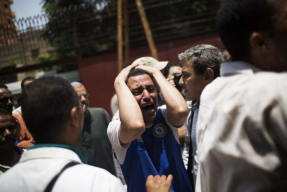 An Egyptian man cries outside a morgue after carrying the corpse of his brother killed near the Republican Guard building in Cairo, Egypt, Monday, July 8, 2013. Egyptian soldiers and police opened fire on supporters of the ousted president early Monday in violence that left dozens of people killed, including one officer, outside a military building in Cairo where demonstrators had been holding a sit-in, government officials and witnesses said. (AP Photo/Manu Brabo) Photo: Manu Brabo, Associated Press