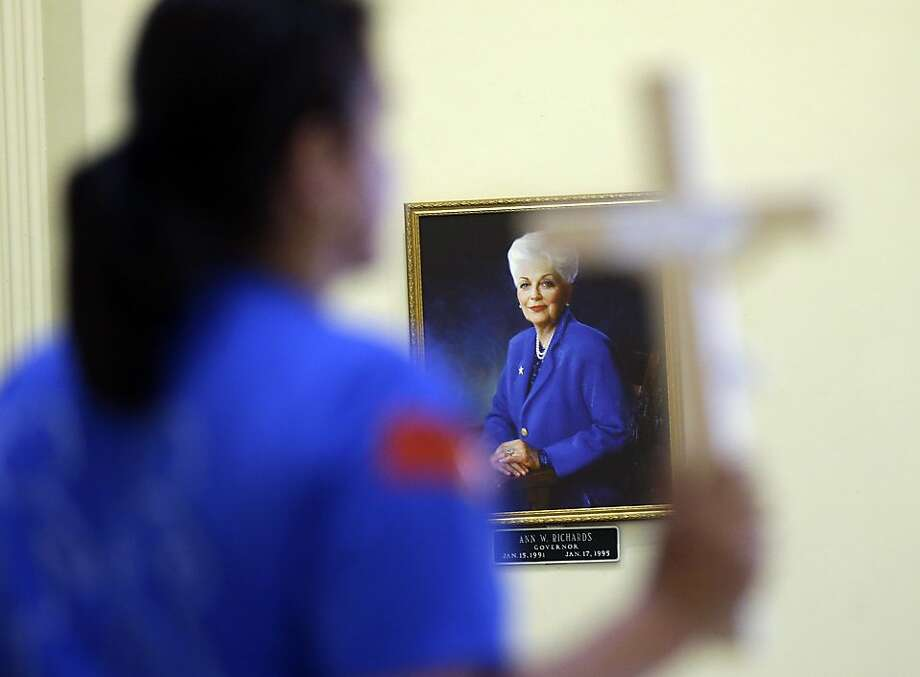 A portrait of former Texas Gov. Ann Richards is displayed as an anti-abortion demonstrator holds a cross in the rotunda of the Texas Capitol, Monday, July 8, 2013, in Austin, Texas. The fight over access to abortion in Texas resumed Monday, with a Senate hearing and a nighttime anti-abortion rally at the Capitol. (AP Photo/Eric Gay) Photo: Eric Gay, Associated Press
