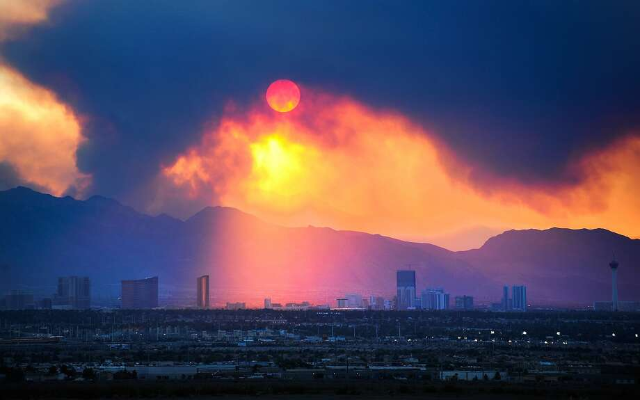 The Las Vegas Strip skyline is seen as smoke continues to billow from the Carpenter 1 fire on Mount Charleston on Monday, July 8, 2013 in Las  Vegas.  Homes were threatened, but more than 750 firefighters, including 18 elite Hotshot crews, were battling the Carpenter 1 Fire some 25 miles northwest of Las Vegas, said Jay Nichols, a U.S. Forest Service spokesman in the Spring Mountains National Recreation Area.  (AP Photo/Las Vegas Review-Journal, David Becker) Photo: David Becker, Associated Press