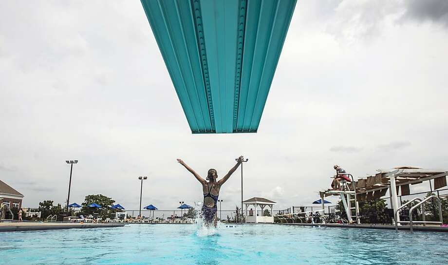 Grace Crawford, 12, dives into the swimming pool Monday, July 8, 2013, at Danville Country Club in Danville, Ky. (AP Photo/The Advocate Messenger, Clay Jackson) Photo: Clay Jackson, Associated Press