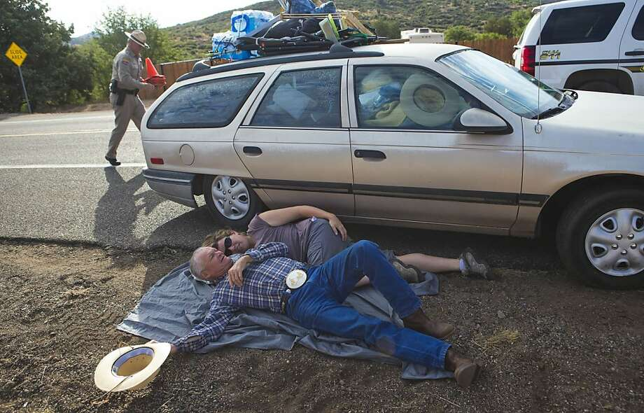 Tex Gilligan, of Yarnell, Ariz., bottom, and his caregiver, Joy Collura, from Congress, Ariz., lay in the shade while waiting at a check point on Hwy 89 near Yarnell, Ariz. on Monday, July 8, 2013, as evacuees from Yarnell and Illah are let back into their homes after being evacuated June 30. Nineteen members of the Granite Mountain Hotshot crew died fighting the Yarnell Hills Fire, about 40 miles southwest of Prescott. (AP Photo/The Arizona Republic, Michael Chow)  MARICOPA COUNTY OUT; MAGS OUT; NO SALES Photo: Michael Chow, Associated Press