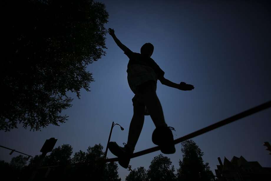 Noah Fortner,15, is silhouetted, as he walks on a slack line, along Elmwood Ave, near Bidwell Parkway, in Buffalo, N.Y. on Monday, July 8, 2013. (AP Photo/The Buffalo News, Harry Scull Jr.) Photo: Harry Scull Jr., Associated Press