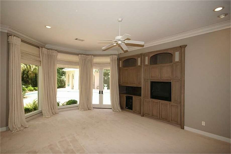The master bedroom has large windows, neutral carpeting and built-ins.