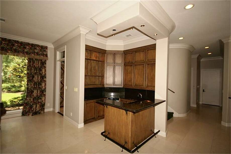 The guest kitchen has wood cabinets, a granite countertop island and a wine closet.