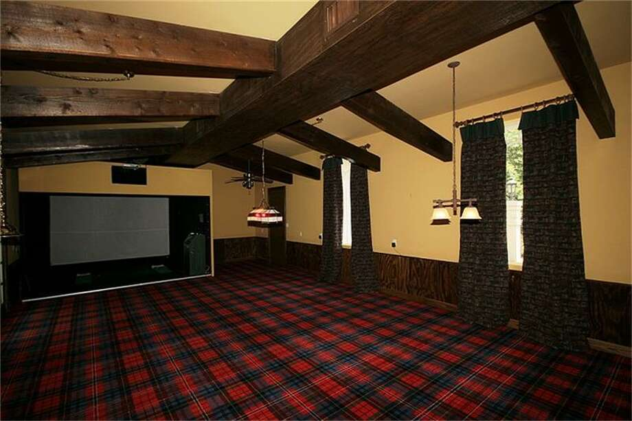 The media room has plenty of space for a large television and an exposed beam ceiling.