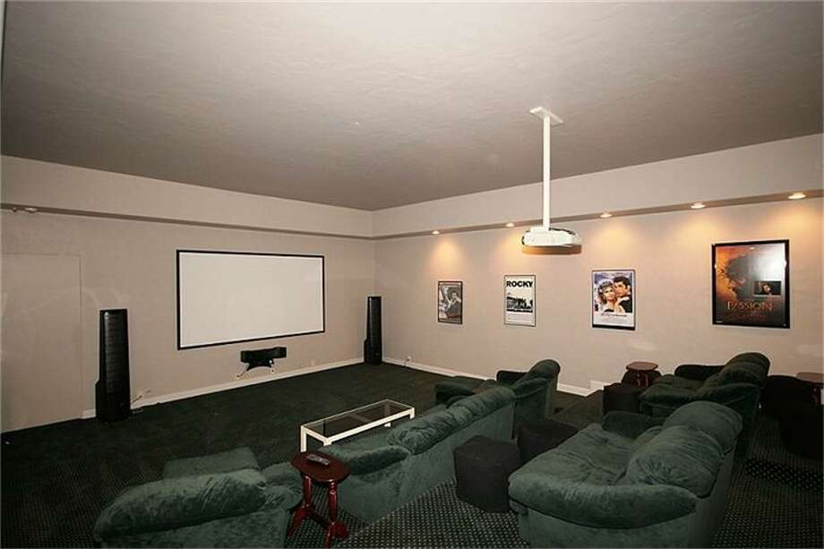 The theater room has a projector and recessed lighting.