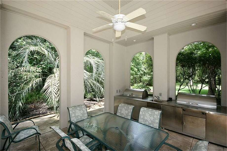 The covered patio with outdoor kitchen offers a spacious area for outdoor entertaining.