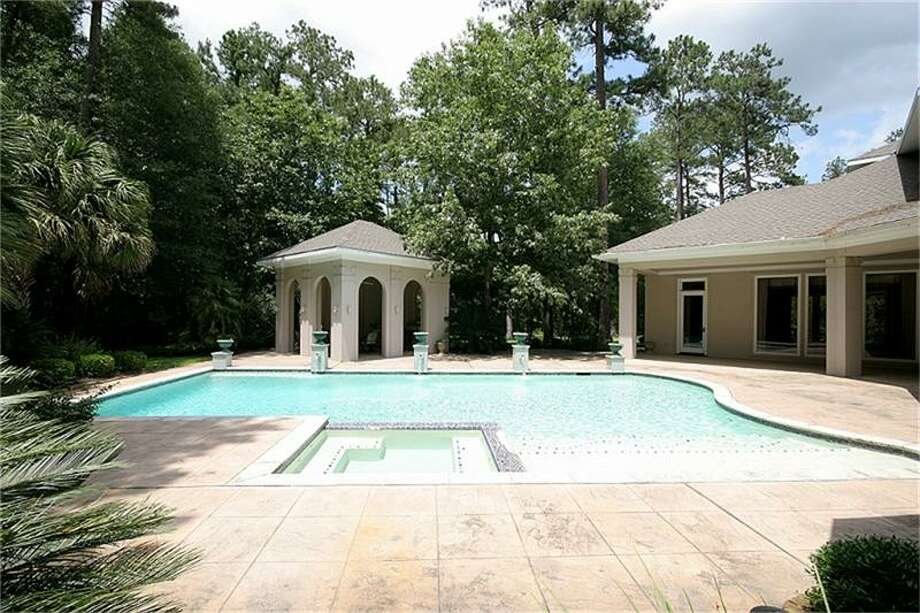 The pool is near the outdoor kitchen and covered patio.