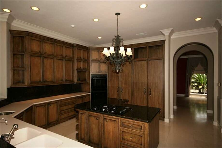 The kitchen features wood cabinets and a L-shaped, granite countertop island.