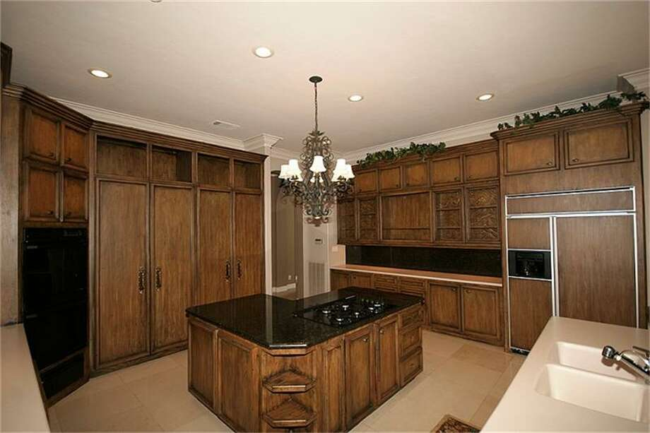 The kitchen offers plenty of built-in cabinet space for storage.