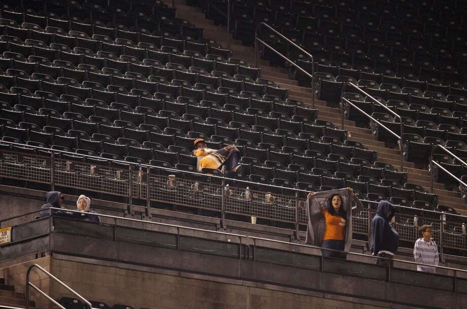 The Gians' faithful fans watch from the nearly empty view level late into the night and early morning for the end of the game. The San Francisco Giants played the New York Mets at AT&T Park in San Francisco, Calif., on Monday, July 8, 2013, losing 4-3 in 16 innings.