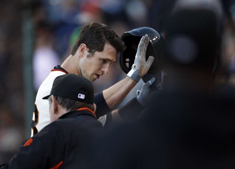 Buster Posey returns to the dugout after hitting a two run homerun in the first inning. The San Francisco Giants played the New York Mets at AT&T Park in San Francisco, Calif., on Monday, July 8, 2013.