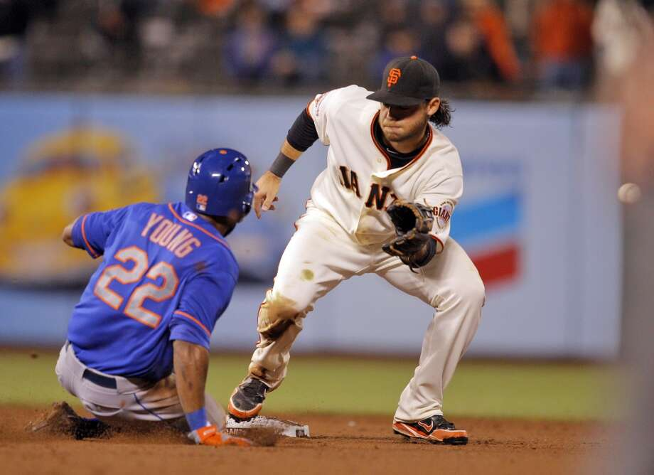 Brandon Crawford can't get a handle on a ball from Buster Posey as Eric Young steals second in the sixteenth inning. Young would later score the winning run. The San Francisco Giants played the New York Mets at AT&T Park in San Francisco, Calif., on Monday, July 8, 2013, losing 4-3 in 16 innings.