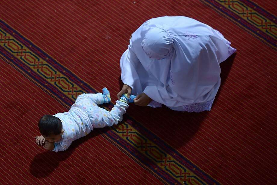 Where do you think you're going? A Muslim mother nips an exploratory expedition in the bud during Ramadan prayers at the Istiqlal mosque in Jakarta. Photo: Adek Berry, AFP/Getty Images