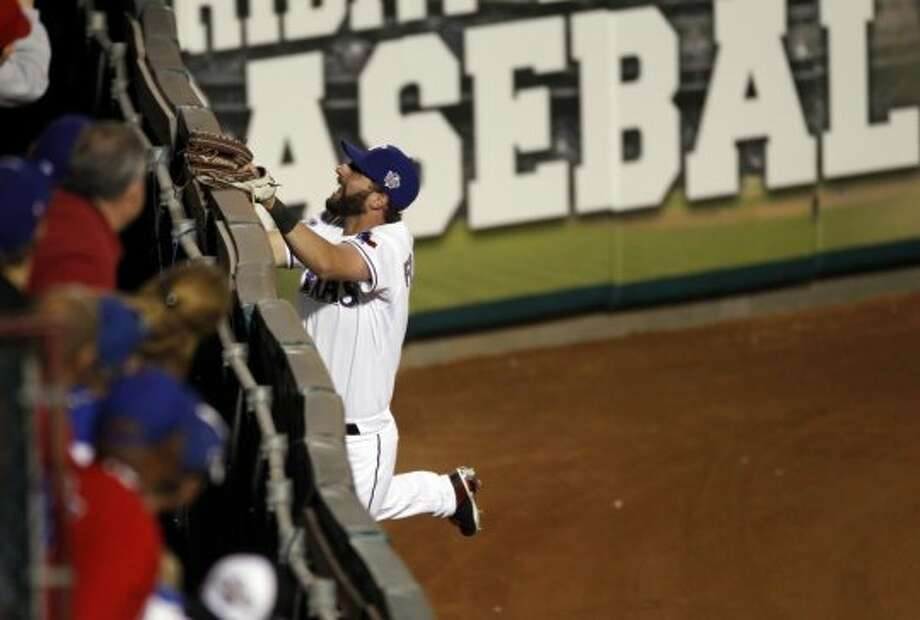 The Rangers' Jeff Francoeur leaps up against the wall chasing a home run hit by the Giants' Andres Torres in the eighth inning of Game 3 of the World Series at Rangers Ballpark. Photo: Carlos Avila Gonzalez, San Francisco Chronicle