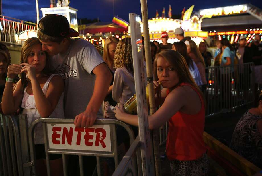 The third wheel: Sarah Kalac and Sam Turner cozy up in line for the Power carnival ride as 